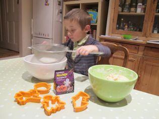 Kids baking sieve flour