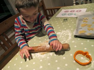 kids baking, using rolling pin with cookie dough