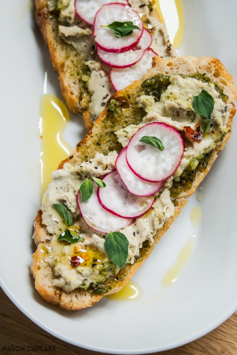 White bean hummus with homemade pesto on focaccia toast - easy to make with canned beans or dried pulses as a summer appetiser, vegetarian bean dip or sandwich filling