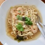 White bowl of tom yum prawn noodle soup recipe with fresh coriander garnish