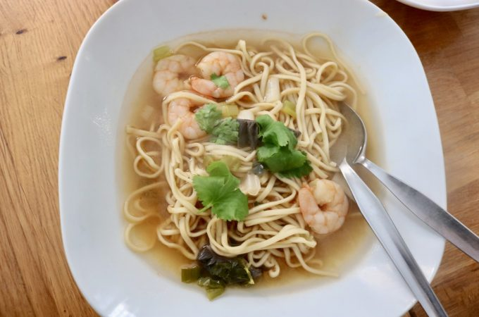 White bowl of tom yum prawn noodle soup recipe with fresh coriander garnish