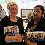 Two ladies holding Masterchef books with Gregg Wallace behind them