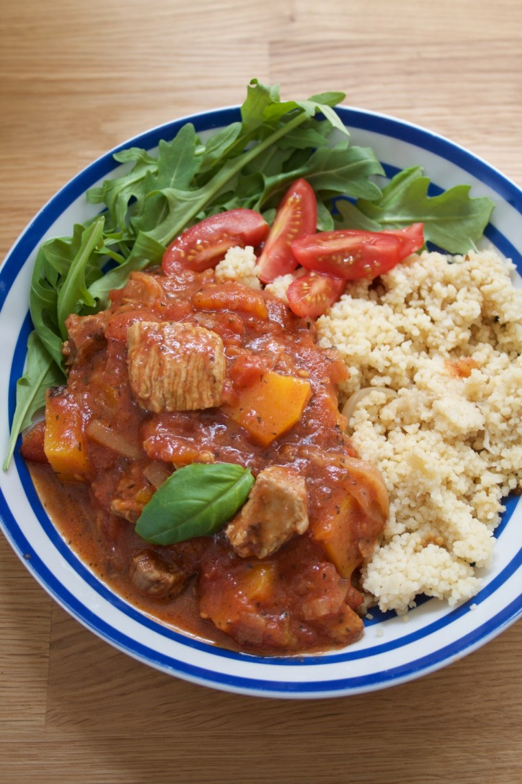 Turkey Thigh Tagine stew served in a blue stripey bowl alongside rocket and cous cous - portrait