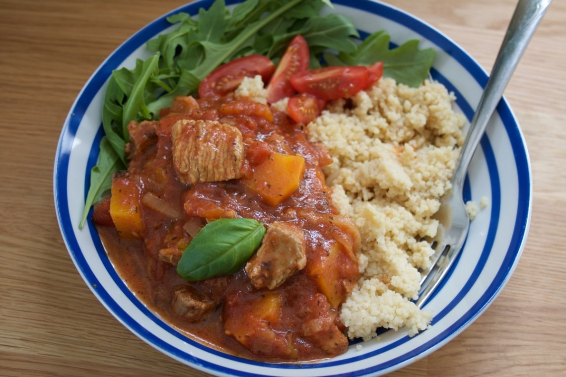 Turkey Thigh Tagine stew served in a blue stripey bowl alongside rocket and cous cous - landscape
