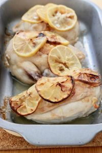 Oven dish with three chicken supreme pieces with lemon slices - portrait layout
